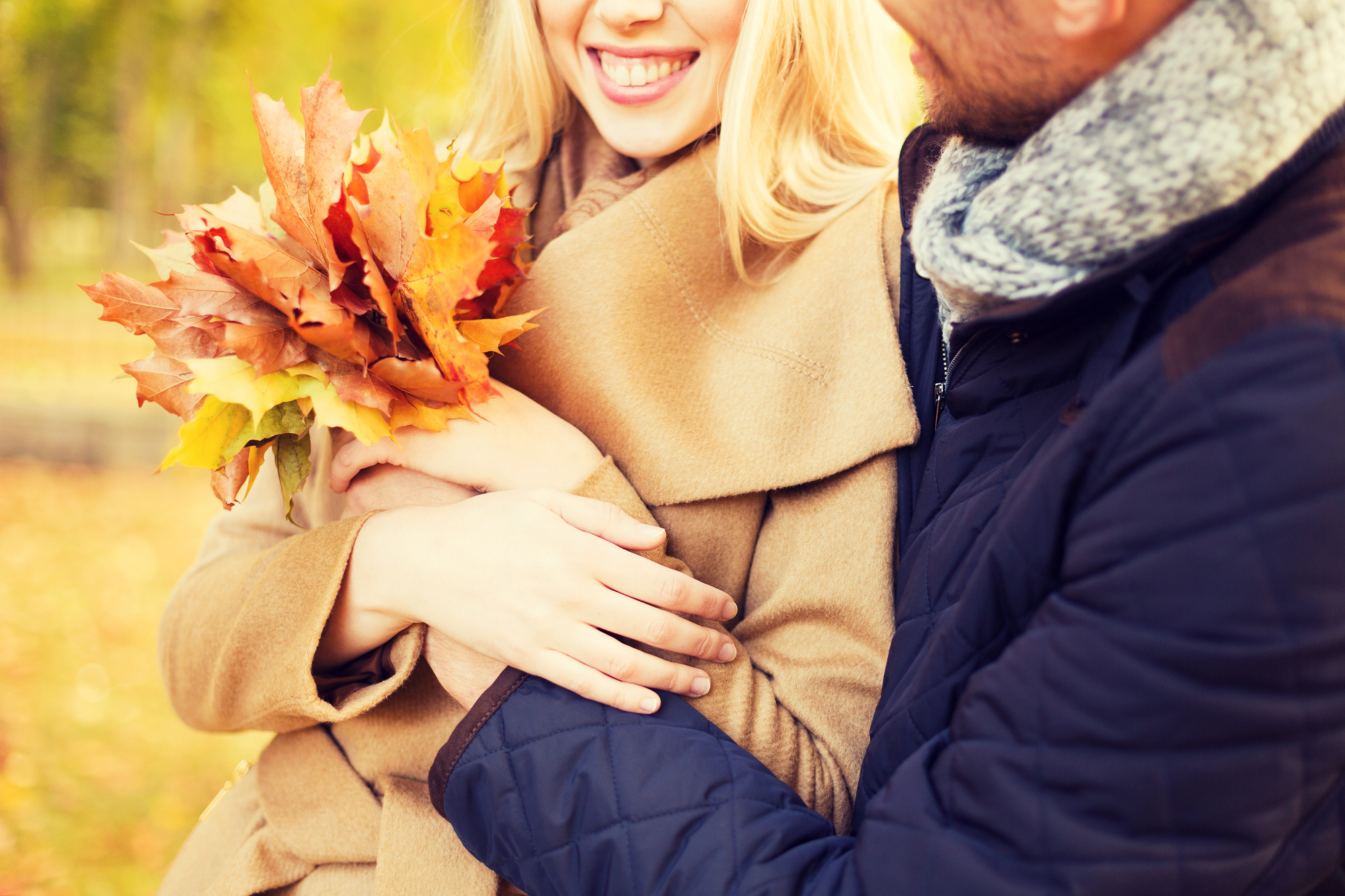 love, relationship, family and people concept - close up of smiling couple with bunch of leaves hugging in autumn park