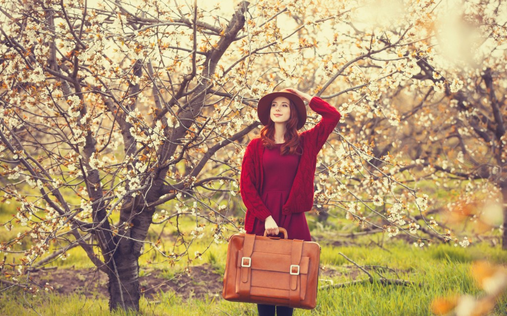Portrait of a beautiful redhead women in red sweater and hat with suitcase in blossom apple tree garden in spring time on sunset.