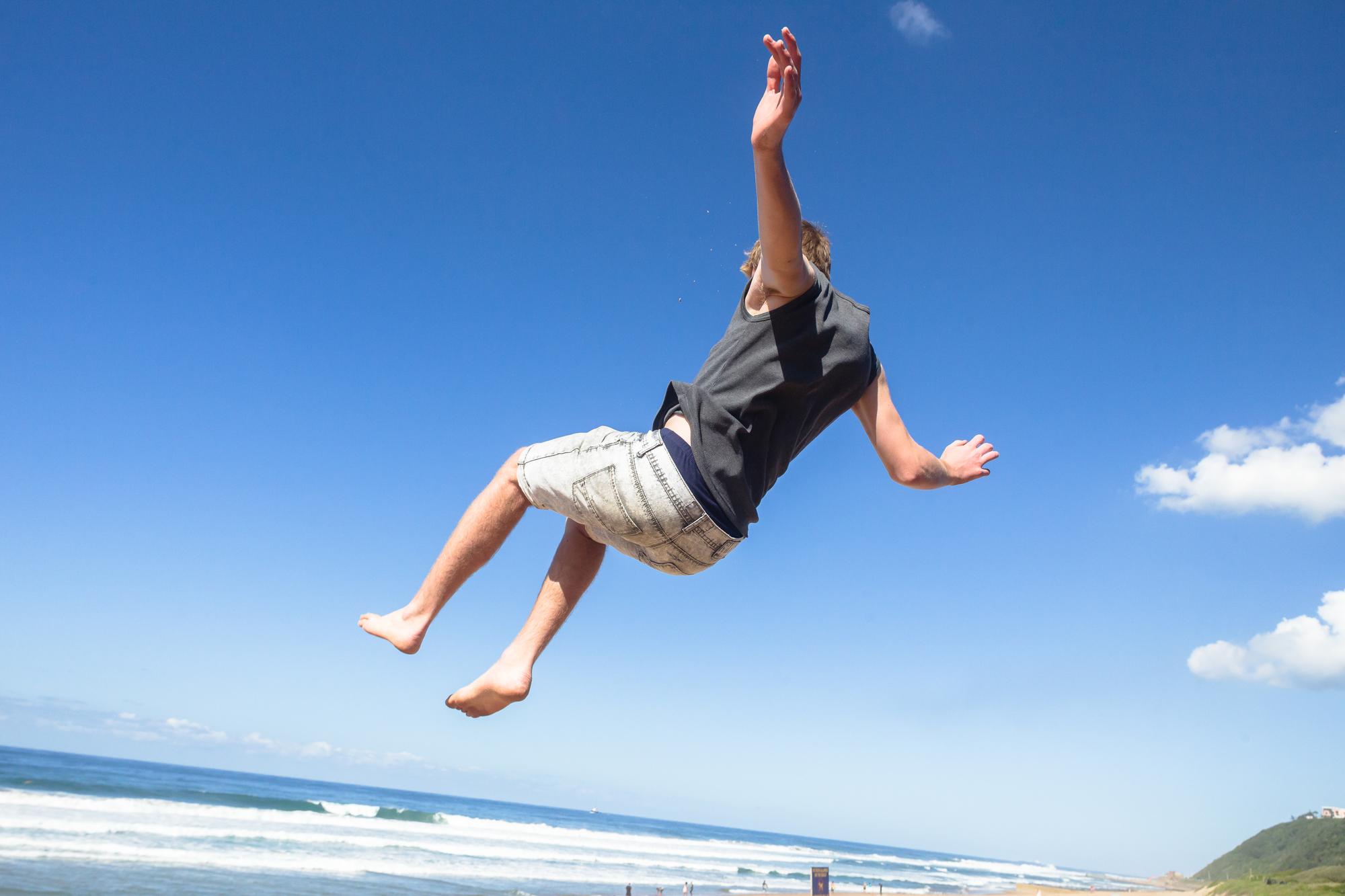 Teen boy jumping off wall into summersault flips on beach