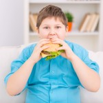 Huge cheeseburger. Chubby boy is taking a big bite off huge burger.