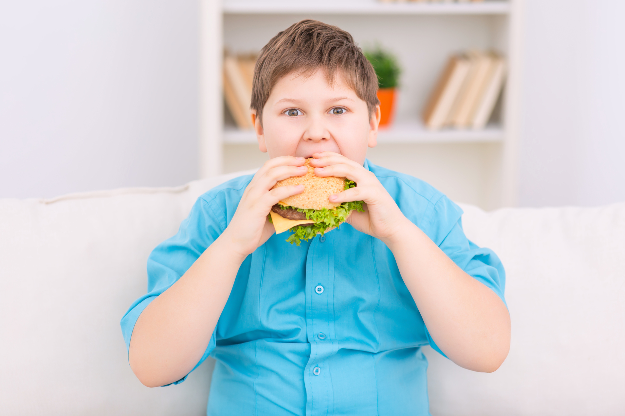 Huge cheeseburger. Chubby boy is taking a big bite off huge burger.