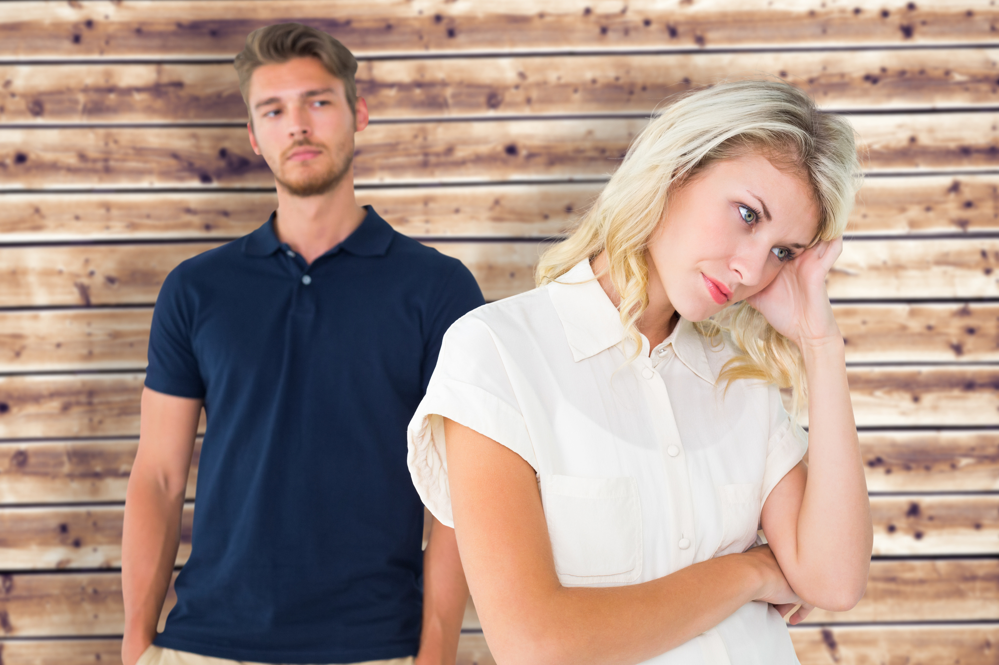 Young blonde not listening to boyfriend against wooden planks background