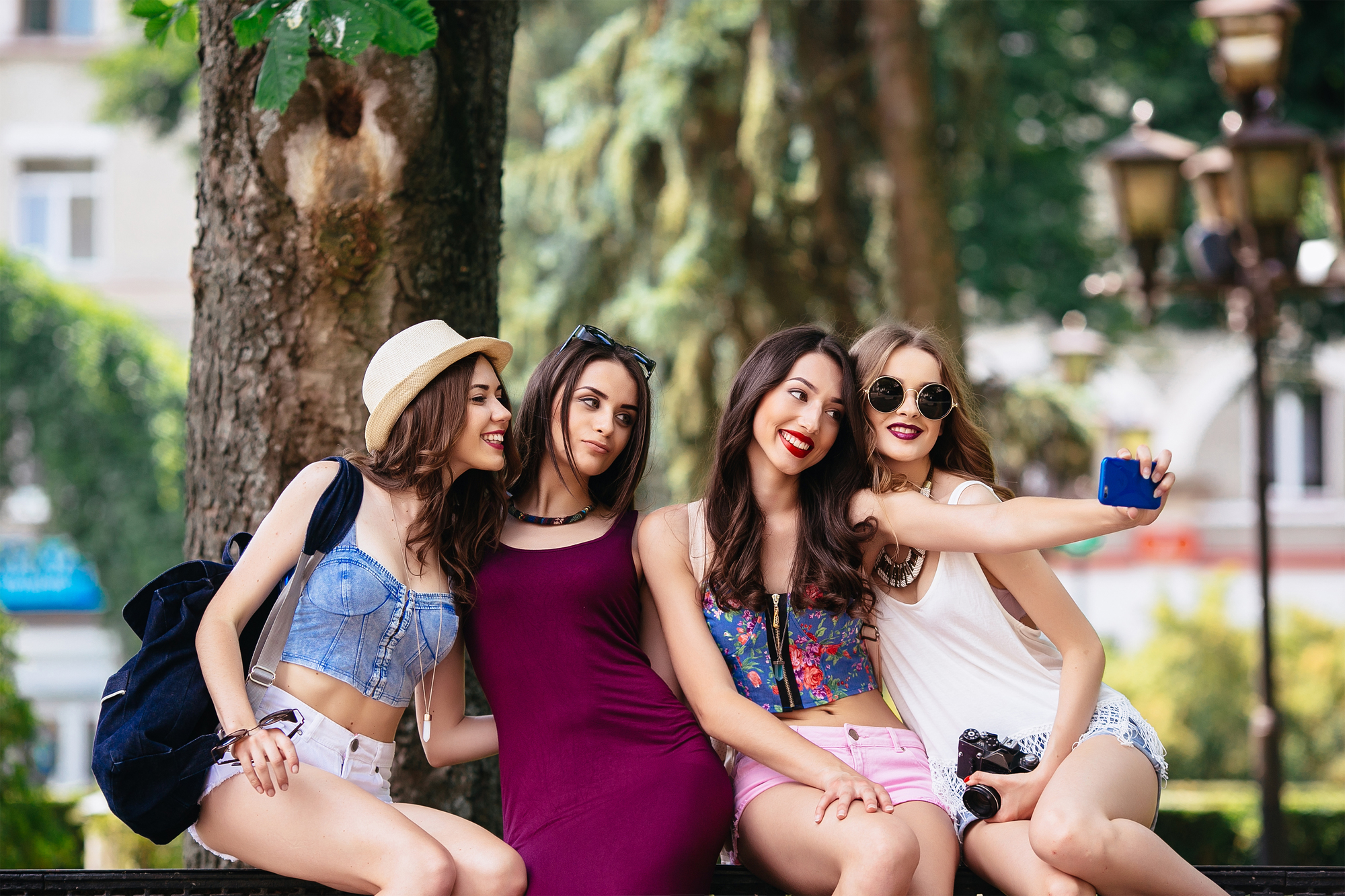 four beautiful young girls make selfie in the park