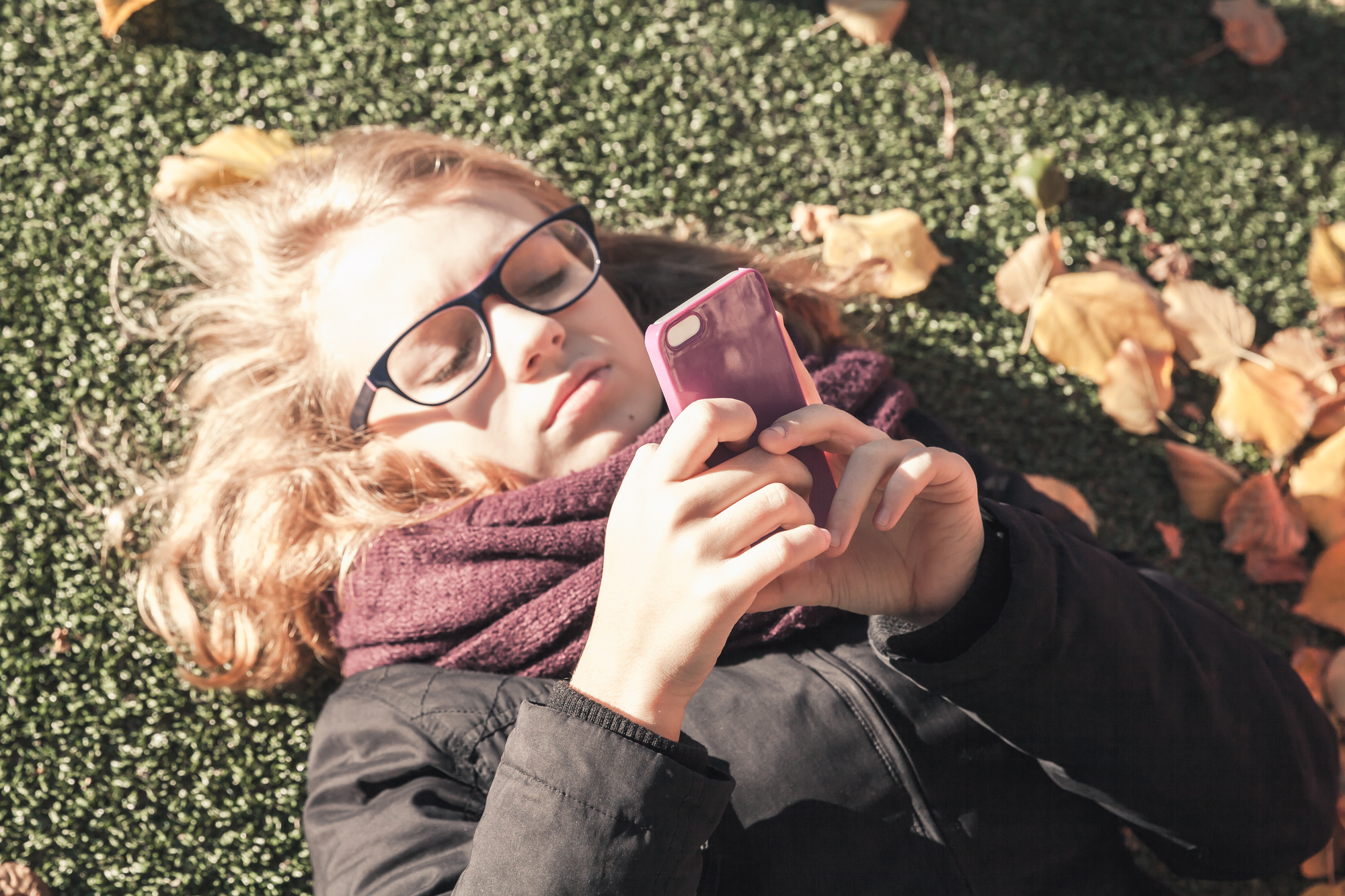 Caucasian blond teenage girl laying in autumnal park and using smart phone, vintage style tonal correction photo filter