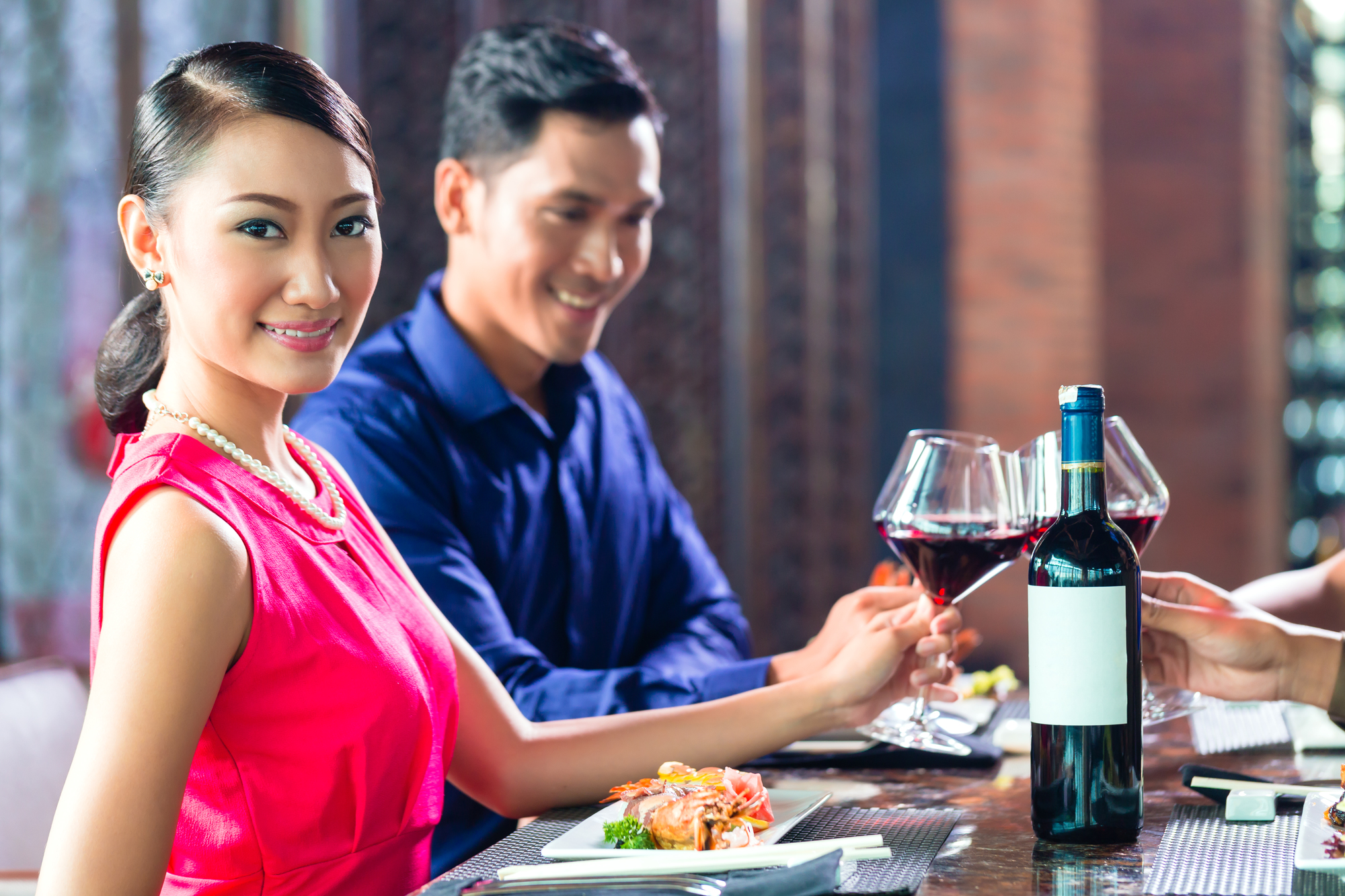 Asian Friends celebrating with red wine in restaurant