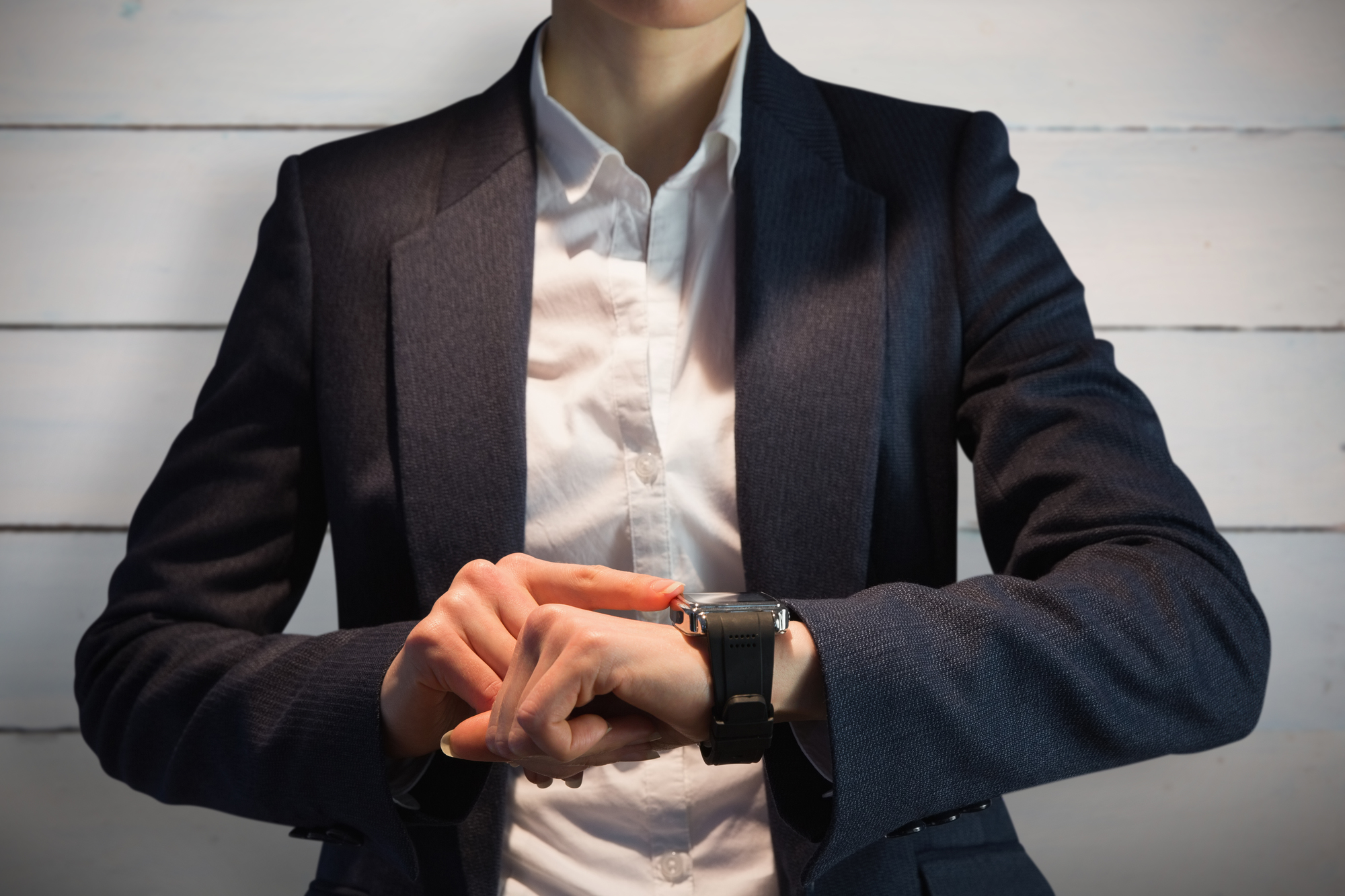 Businesswoman using watch against painted blue wooden planks