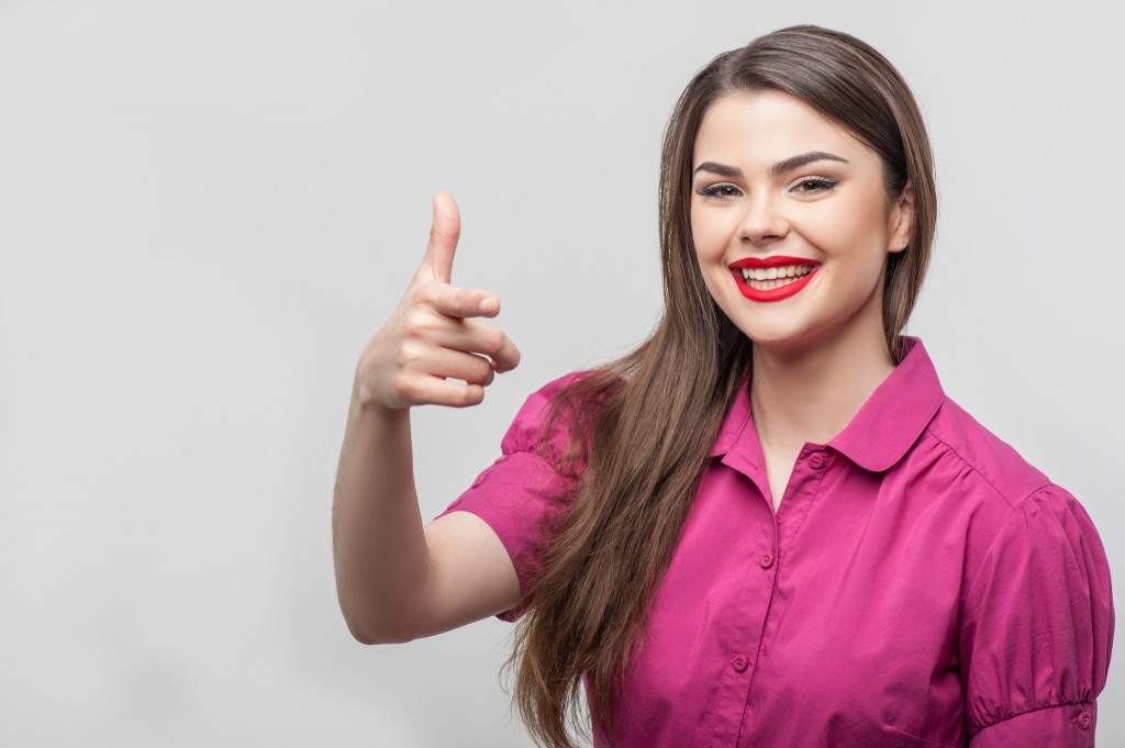 Waist up portrait of beautiful girl reporter with Caucasian appearance, who is smiling and looking at the camera and raising her right hand in such way as if she were trying to shoot someone in jest, isolated on a grey background and there is copy place in the left side