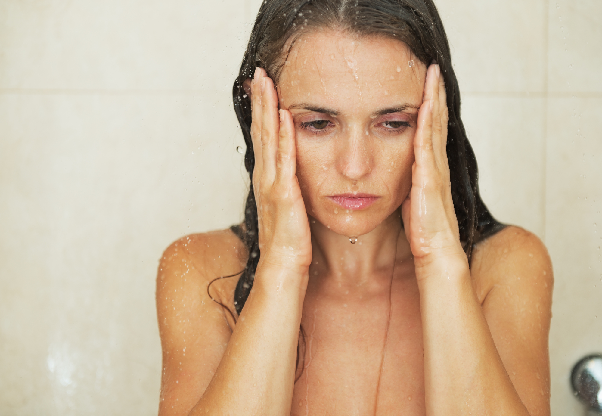 Portrait of stressed young woman in shower
