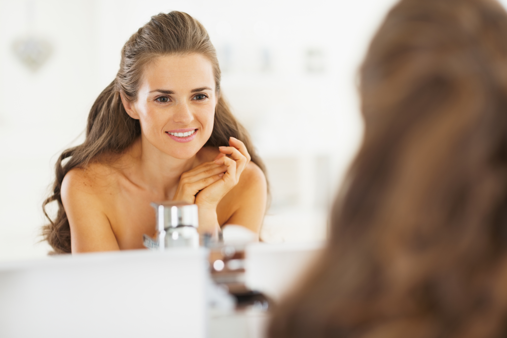 Portrait of happy young woman looking in mirror in bathroom