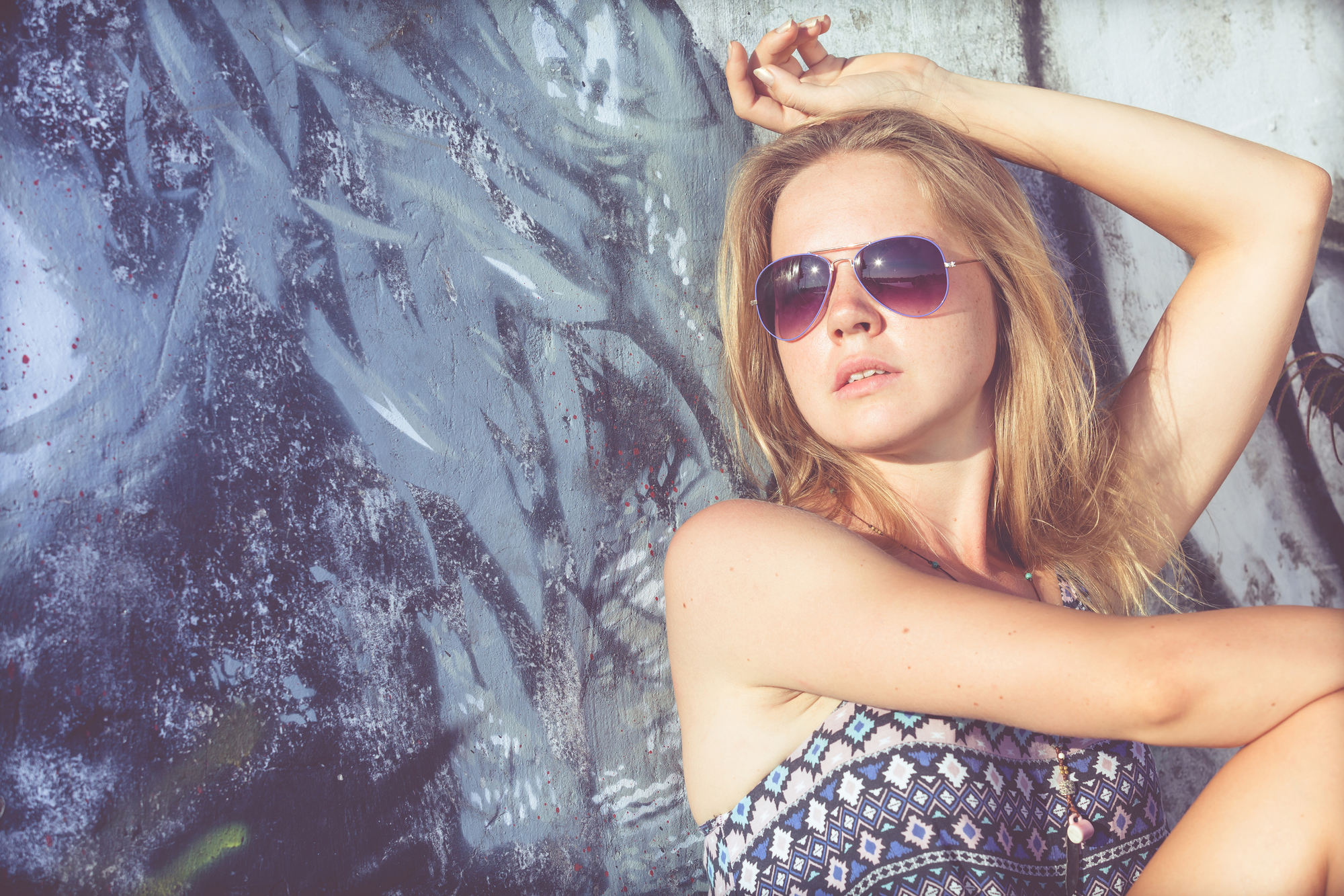 portrait of a beautiful blonde girl with sunglasses sitting near the wall at the day time