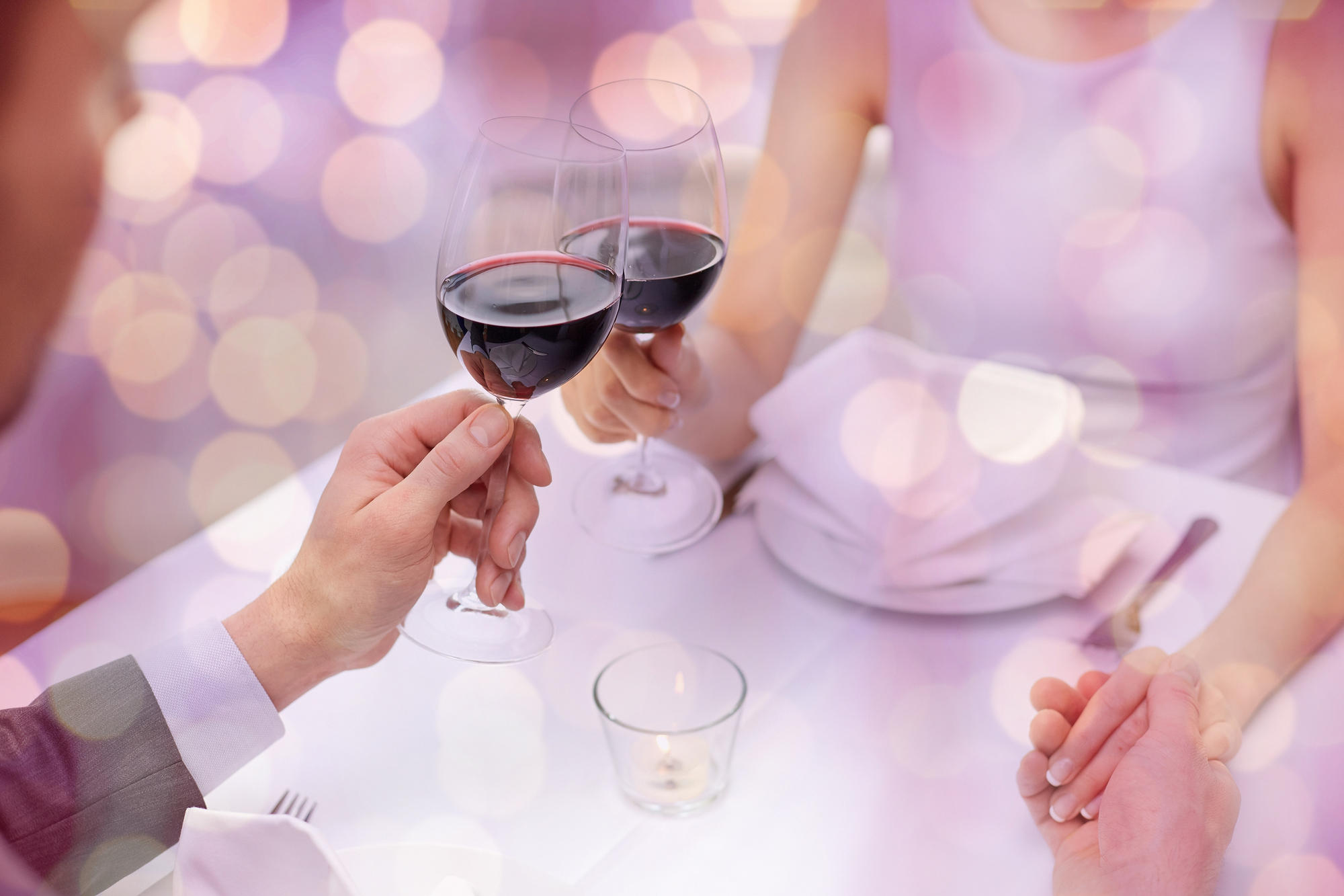 restaurant, people, celebration and holiday concept - close up of young couple with glasses of red wine at restaurant over violet holidays lights background