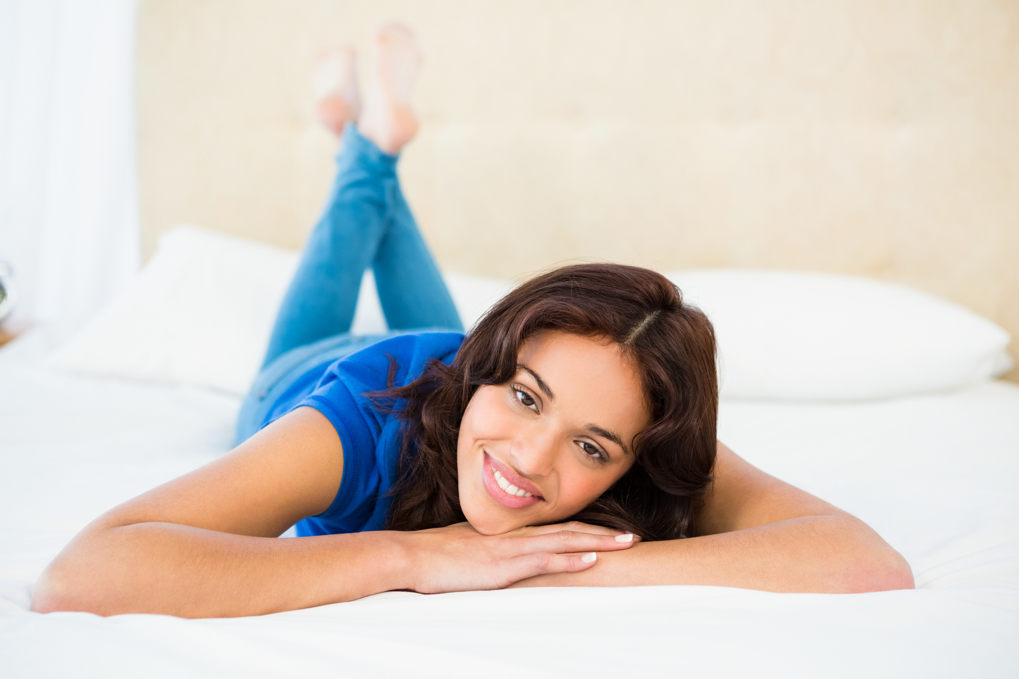 Smiling woman using smartphone while lying on bed at home
