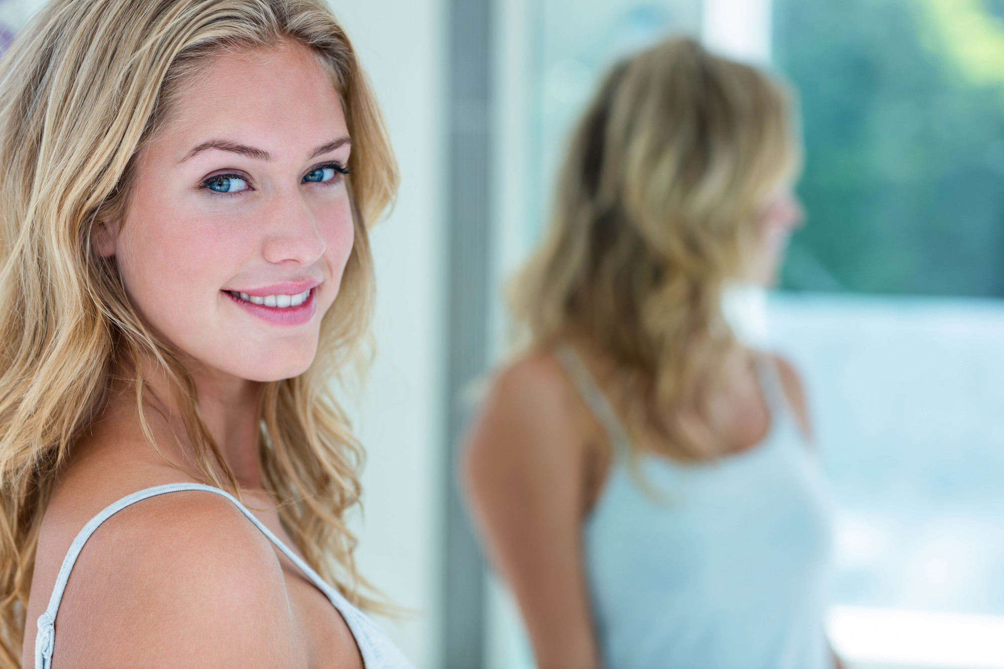 Smiling beautiful young woman looking at herself in the bathroom mirror at home