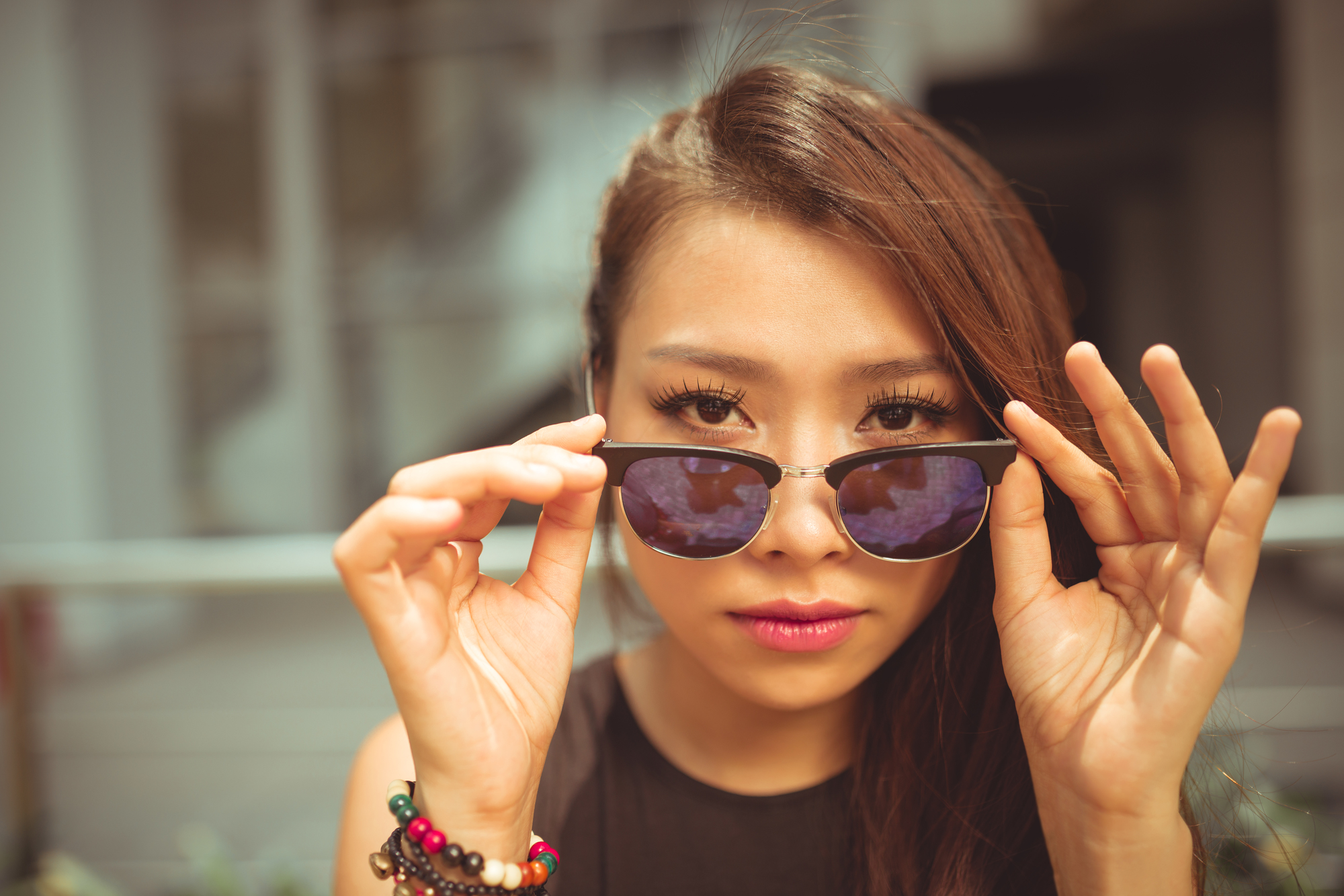 Beautiful Vietnamese woman with sunglasses looking at camera