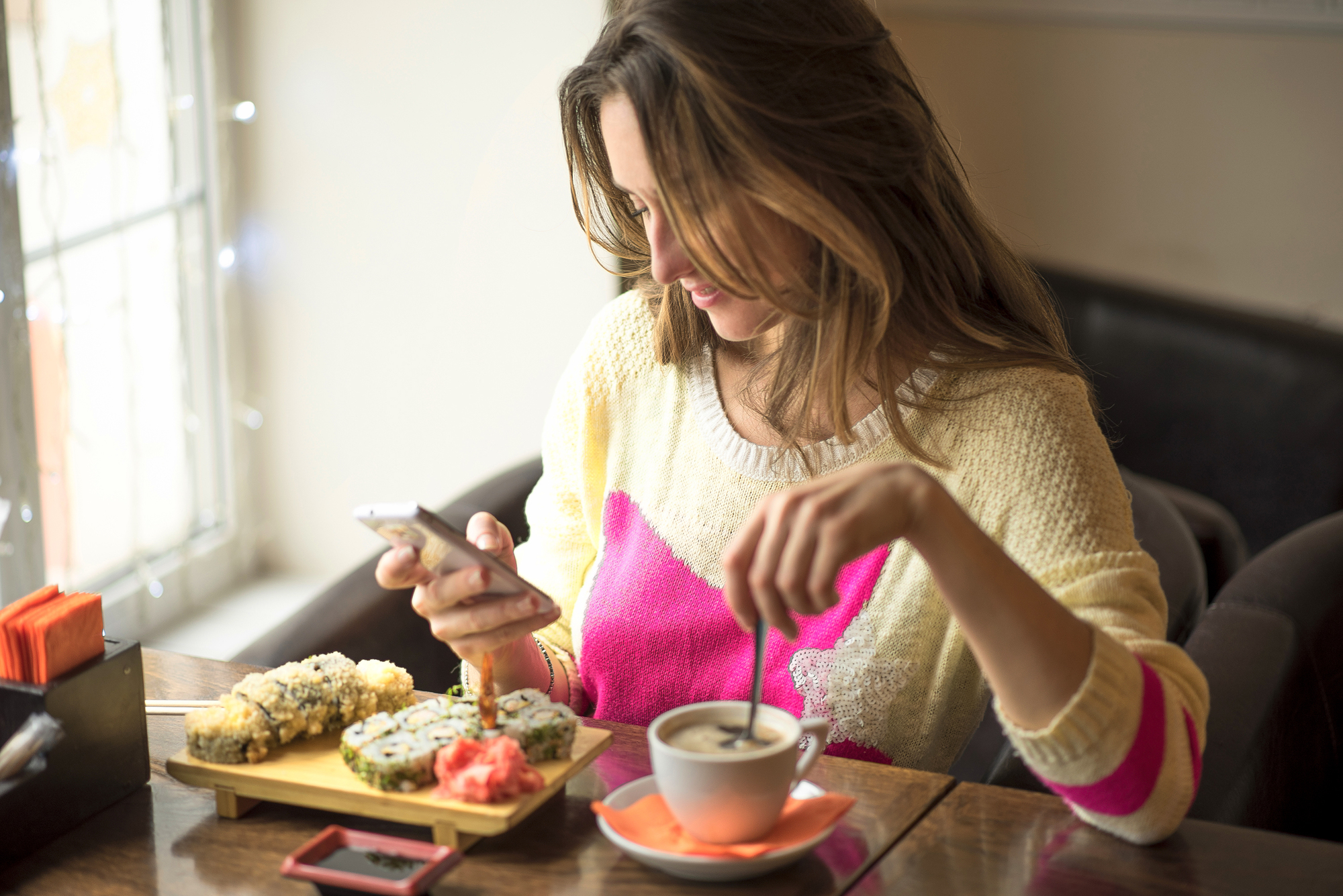 Young business woman eating sushi for lunch at a small cafe and a healthy lifestyle, working on a smartphone coffee. Happy smiling, fashionable, in a yellow sweater.