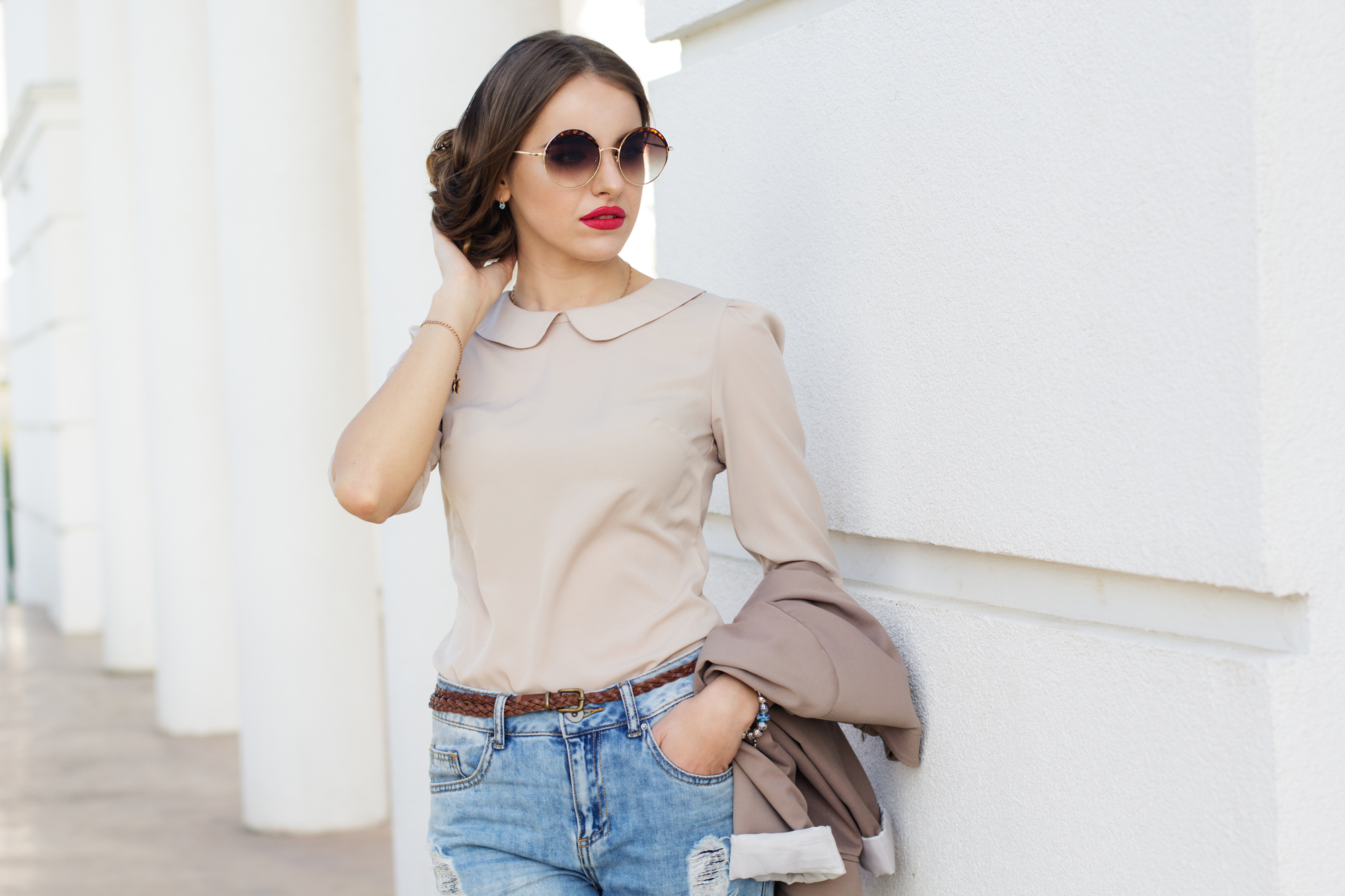Beautiful business lady is wearing sunglasses and holding jacket infront of white wall