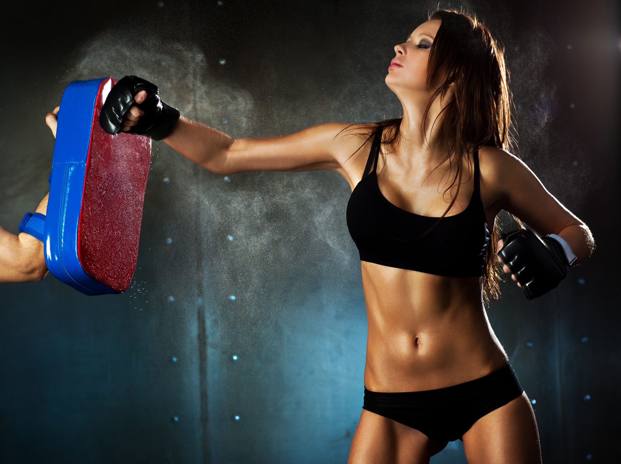 Young sexy woman hitting punching bag.