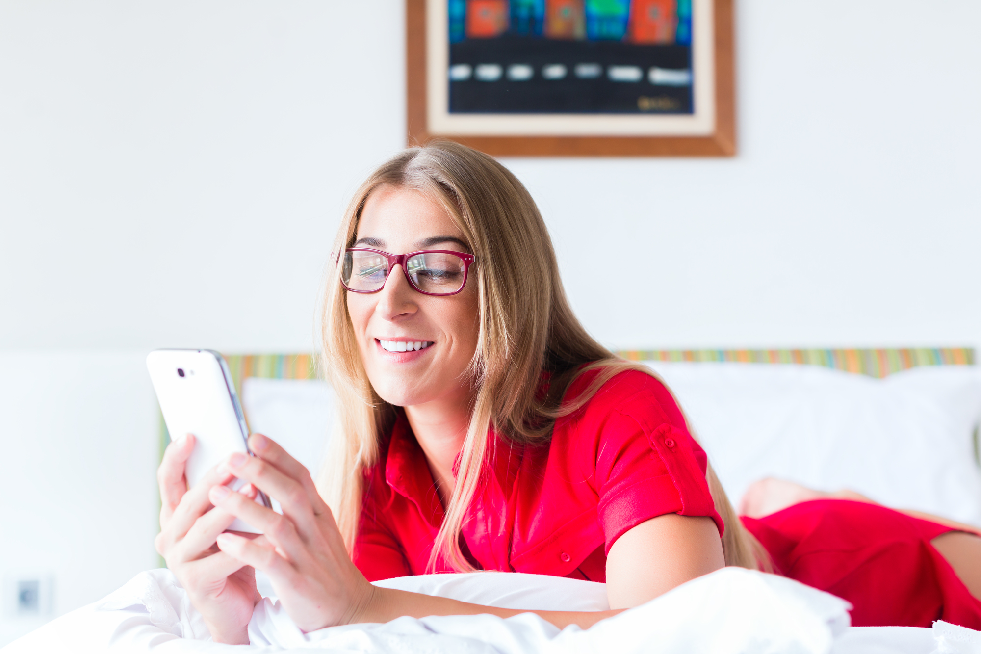 Woman reading Mails on smartphone on bed