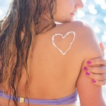 Sunscreen tan lotion heart shape drawing on woman back over blue sea background