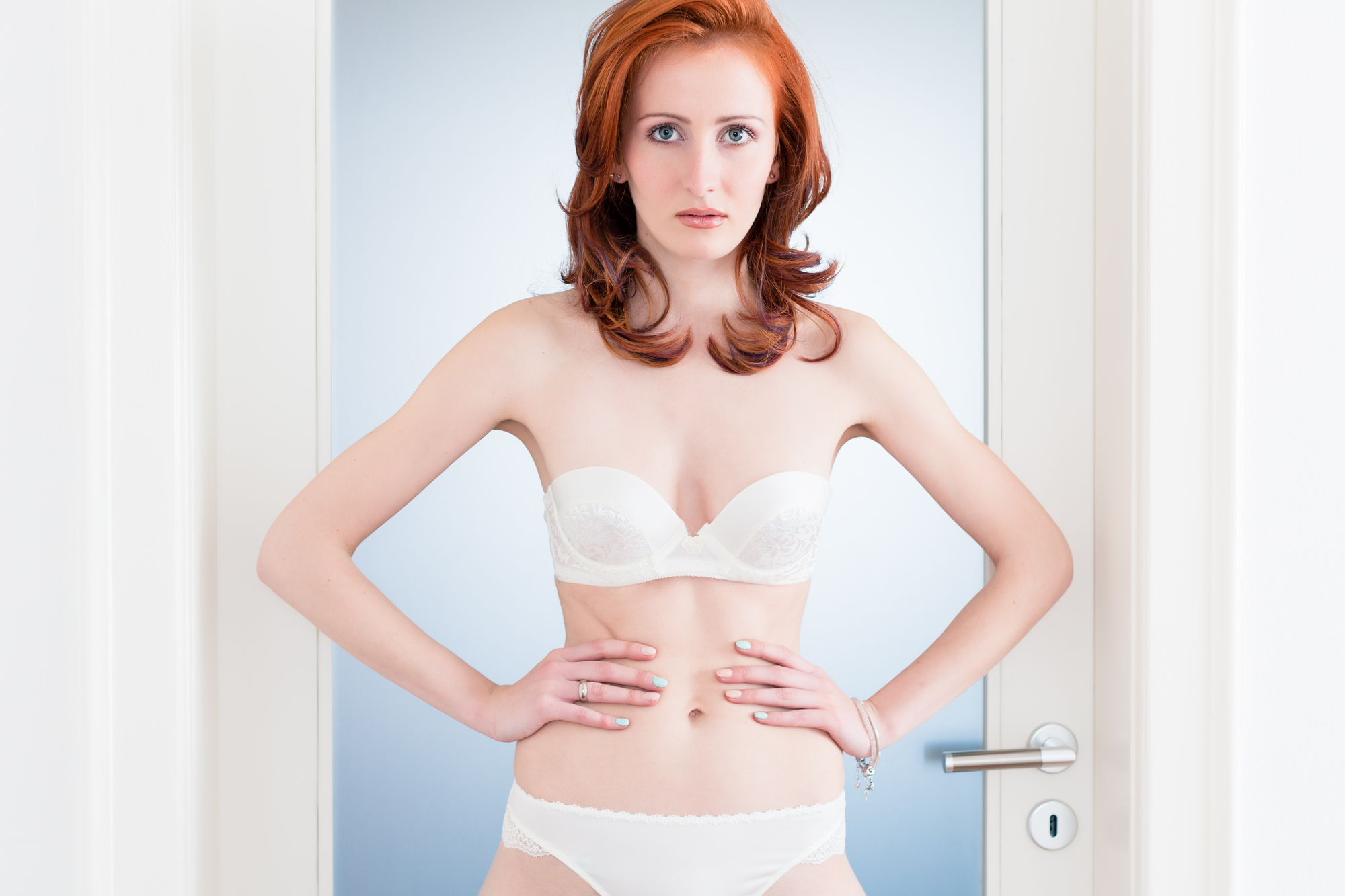 Bride in bridal lingerie standing in home