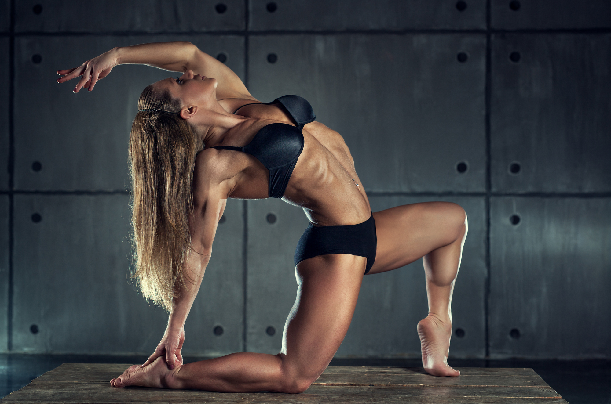 Strong woman bodybuilder on wall background.