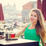 Young Woman Drinking Tea in a Cafe Outdoors. Summer City Background. Shallow Depth of Field. Toned Photo.