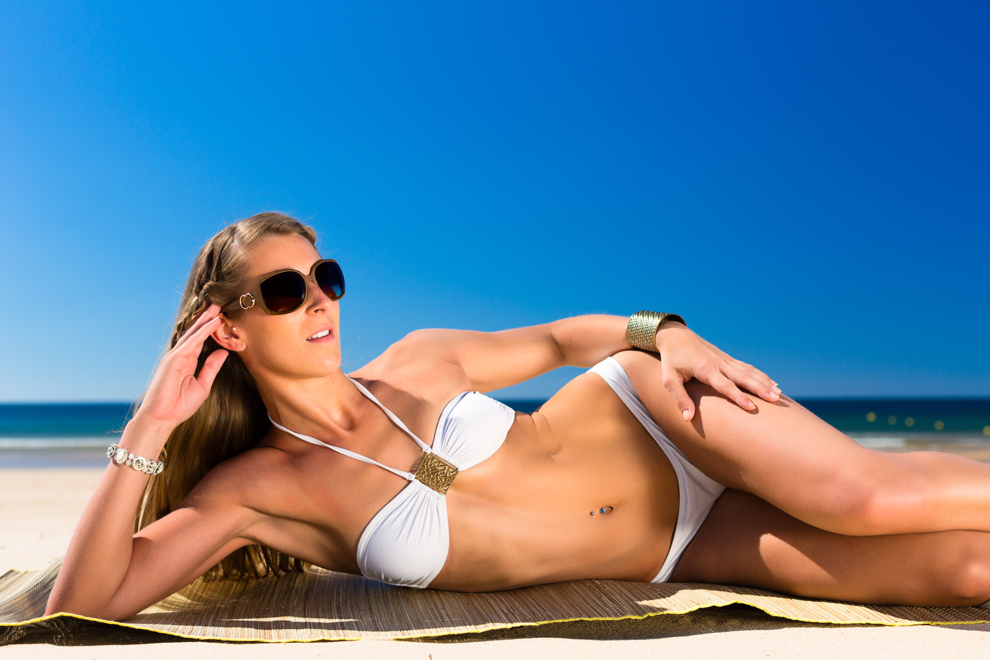 Attractive Woman in white bikini sitting in the sun on beach, a lot of copyspace in the blue sky