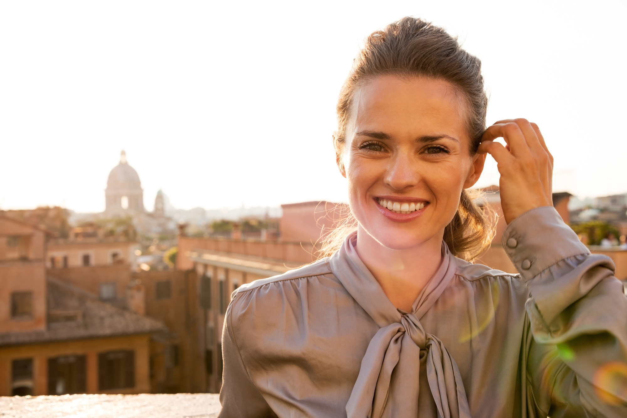 Portrait of happy young woman standing on street overlooking rooftops of rome on sunset