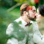 Beautiful couple kissing among spring foliage. Close up portrait of bride and groom at wedding day outdoor, lit by setting sunlight. Man with bow tie and suspenders, woman in  white dress. Copy space.