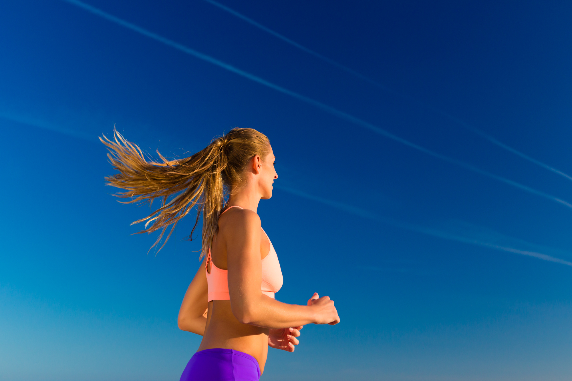 Sport and Fitness - woman jogging under clear blue sky