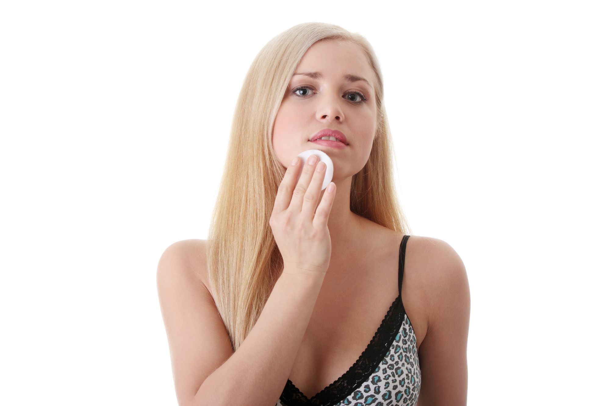 Young blond woman applying face cotton pads. Isolated on white background