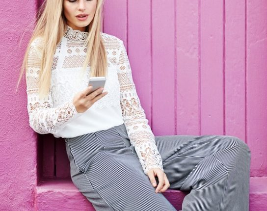Beautiful woman sitting by pink door on cell phone