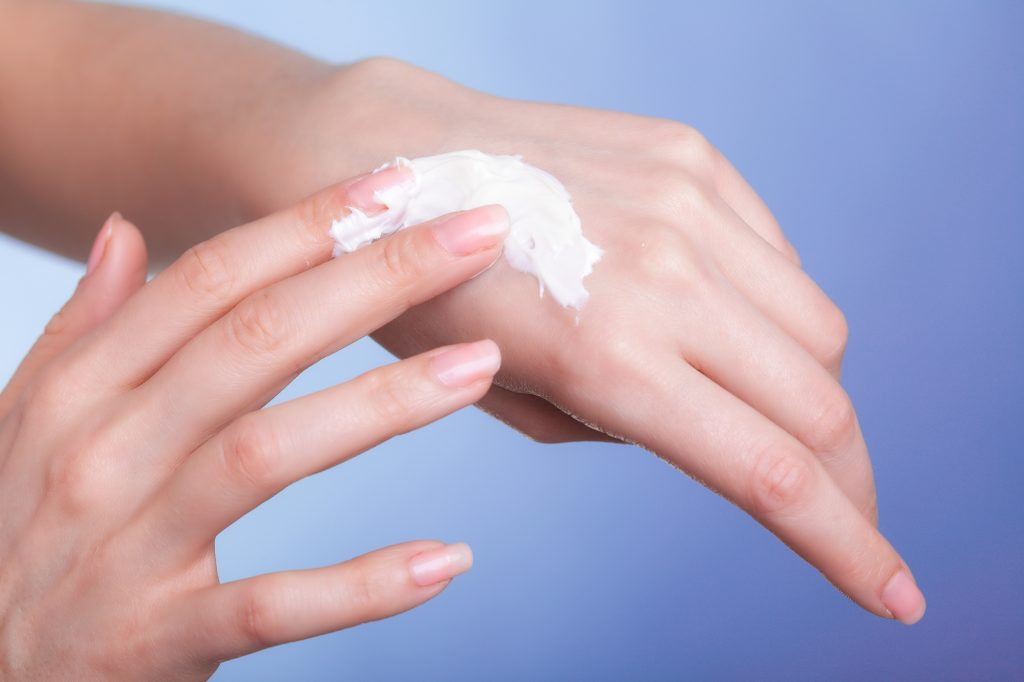 Skincare. Closeup of female hands. Young woman girl taking care of her dry hands palms applying moisturizing cream. Beauty treatment.